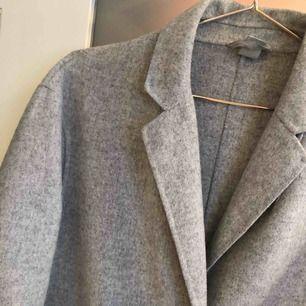 Snygg kappa i ljusgrå fleece med svarta knappar och två stora fickor. Den är varm och skön och är perfekt nu till vintern.  Köparen betalar frakt.