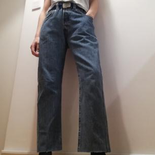 Klassiska Levi's 501 vintage jeans i mellanblå färg med hög midja i stl 33. Avklippta längst ner. Midjemått 88 cm, innerbenslängd 68 cm. Jag på bilden har stl XS och har använt dem oversize med skärp i midjan men passar upp till L tror jag, se mått. Frakt 63 kr.