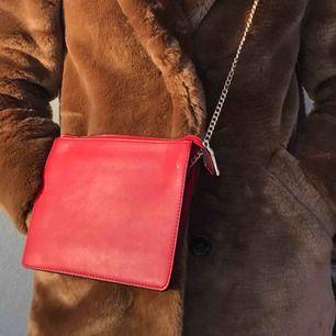 """Söt röd liten väska från Mango. Går att använda som cross-body-bag eller one-shoulder-bag! Den har flera fack inuti(bild tre) och väskremmen består av en guldkedja samt själva """"väsktyget""""!! Möts upp i Stockholm eller skickar!!"""