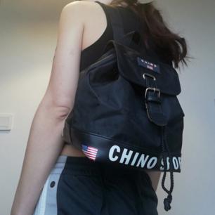 Svart sportig mini-ryggsäck köpt secondhand. Lite Tommy Hilfiger inspirerad. I jättefint skick, enda att anmärka på är att spännet släppt lite, inget som påverkar funktionen och går nog att limma ihop. Säg till så skickar jag bild på det! Frakt 59 kr.