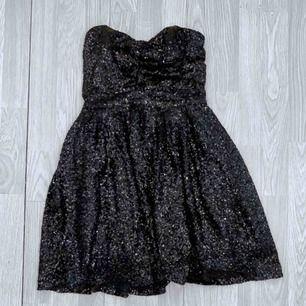 Axelbandslös svart klänning med paljetter. Storlek xs, fint skick.  Möts upp i Stockholm eller fraktar. Frakt kostar 63kr extra, postar med videobevis/bildbevis. Jag garanterar en snabb pålitlig affär!✨