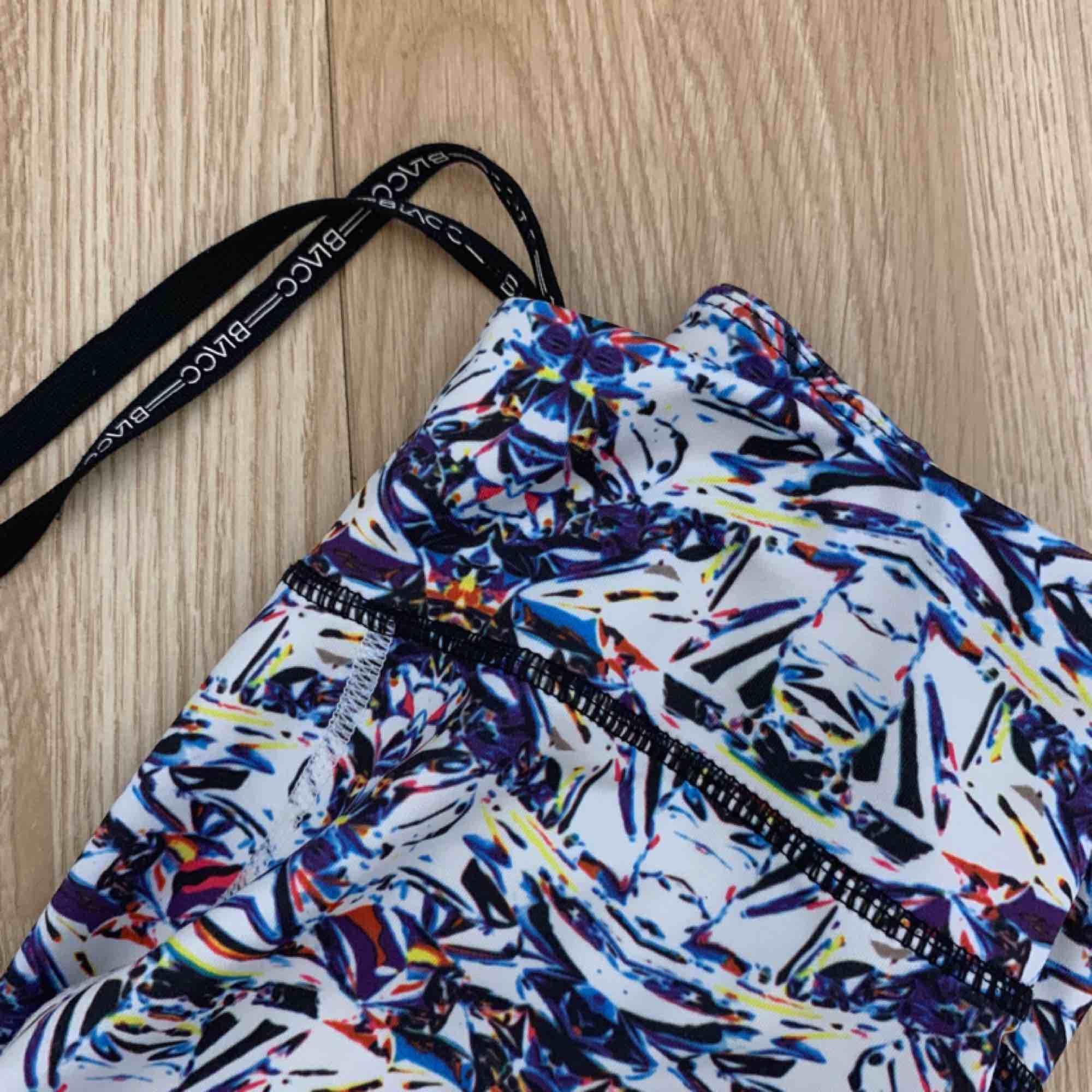 Högmidjade vita/flerfärgade träningstights från Blacc i fint skick. Storlek XS Har svarta mesh detaljer, ficka bak.  Möts upp i Stockholm eller fraktar. Frakt kostar 42kr extra, postar med videobevis/bildbevis. Jag garanterar en snabb pålitlig affär!✨. Jeans & Byxor.