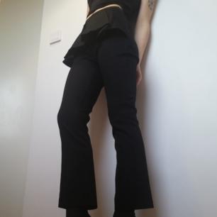 Svarta kostymbyxor med peplum-detalj på framsidan och hög midja från Carin Wester. Lätt utsvängd croppad modell (typ kickflare). Stl 34, normala i storleken. I fint skick. Frakt 59 kr.