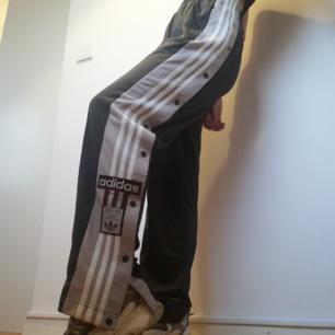 Adidas adicolor popper pants i stl 36. Mörkgrå, beige rand med vita stripes och vinrött märke. Hög midja, ganska långa ben och lite oversize i modellen, jag på bilden är 169 cm och brukar ha stl XS. Frakt 59 kr.