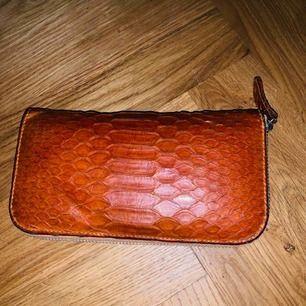 Ormskinn plånbok orange. Knappt använd. Rymlig med många fack