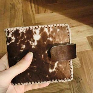 Äkta ko-skinn plånbok i päls. Handgjord i Kenya. Aldrig använt. Haft en likadan tidigare och den har håller i en evighet.