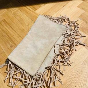 Beige väska med fransar från Gina Tricot. Aldrig använt. Rymlig med tre olika fack