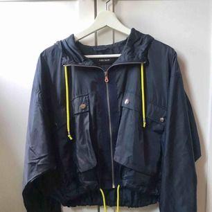 Tunn Marinblå Zara jacka med neon gula detaljer. Sällan använd och är i ett bra skick.
