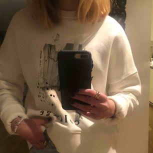 Oversized mysig collegetröja med tryck fram från HM. Använd fåtal gånger. På bilden är ärmarna uppvikta men dem går såklart att vika ner. Storleken är Small och tröjan är helt vit (ser ut som den skiftar lite i färg på bilderna). Köparen står för frakt!