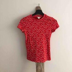 VARA: Röd tunnt ribbad t-shirt med vita blommor från MONKI, ganni inspirerad 🍓  SKICK: inga anmärkningar  MATERIAL: Materiallapp bortklippt