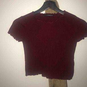 """Croppad vinröd ribbad ljuvlig tröja från Brandy Melville 🥀   Ser ut dom det är en fläck på tröjan men det är det inte, ngt knas med """"ribbningen"""" som gör att det blir så. SKICK: Ett hål på vänster sida längst ner, lätt att sy (se bild)"""