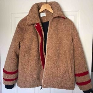 """En jättefin Teddy jacka som har fina röda detaljer. Lite mer än en """"vanlig"""" Teddy jacka. Färgen är i en mörkare brun och den håller värmen väldigt bra."""