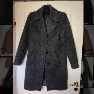 """Mörkgrå kappa som har ett """"lurvigt"""" tyg. Den fäller inte och är rak i passformen. Längden är ungefär vid knäna på någon som är runt 165 cm."""