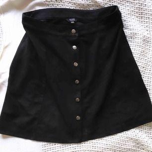 Jättefin svart kjol i skinnkaraktär med silverknappar som går att öppna! Köpt i New York. Superfin till vardag och fest! 🍸   MATERIAL: 100% Polyester
