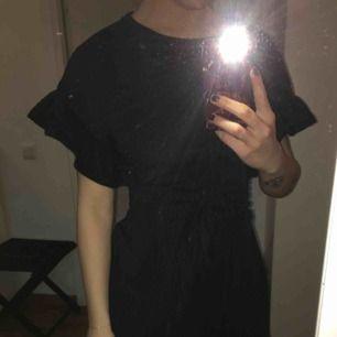 En svart klänning från HM med volanger på slutet av ärmarna och slutet av klänningen. Knappt använd och är i gott skick! Frakt tillkommer på 60kr