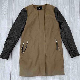 Mörkgrön kappa från HM med svarta skinndetaljer storlek 34. Bra skick förutom en defekt på ärmen  Möts upp i Stockholm eller fraktar. Frakt kostar 63kr extra, postar med videobevis/bildbevis. Jag garanterar en snabb pålitlig affär!✨