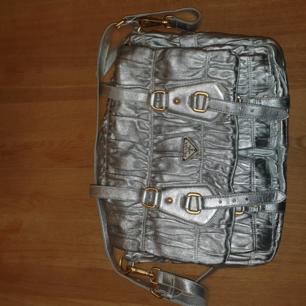 En silvrig vintage axelväska från prada, otroligt sällsynt väska. nypris är ca 40,000 svenska kr säljer billigt för att bli av med den :)
