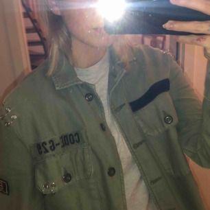 Militärgrön jacka med massa coola detaljer som nitar, kardborrband, ringar osv. Passar perfekt till våren eller hösten med en hoodie under!