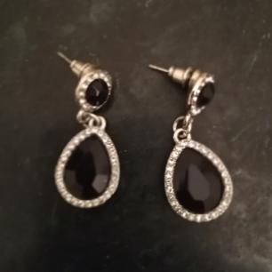 Silvriga örhängen med svarta stenar och strass runtom. Frakt 9 kr.