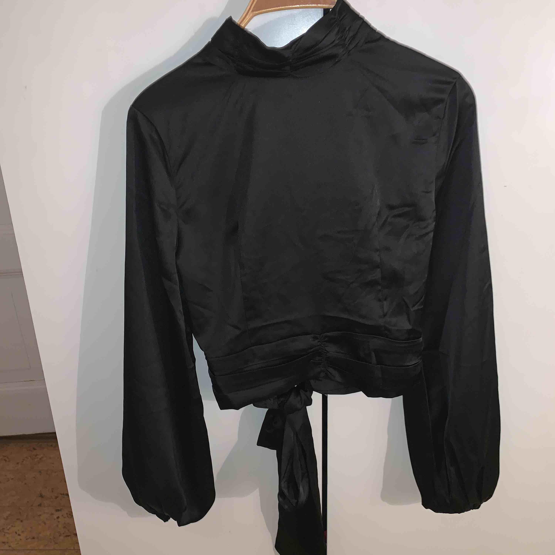 Tröjan är från boohoo. Det är en silkes tröja men öppning i ryggen och snörning nedtill. Den är även lite polo vid halsen och har knappar där bak vid nacken. +frakt. Toppar.