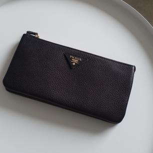 Prada plånbok/clutch i skinn. Väskan har nyckelring för nycklar, plats för kort, mynt, etc. Väldigt praktisk