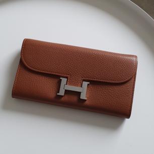 Hermes plånbok i läder. I mycket bra skick, inga skador.  Konjakfärgad skinn med silverfärgade detaljer som man kan se på bilderna.