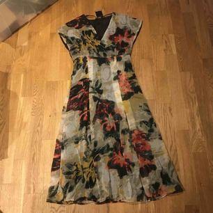 Ny klänning med prislappen kvar 399:- fr Åhlens. Fodrad med svart foder. Yttermaterialet i blommig tunt tyg.  Köparen står för frakt