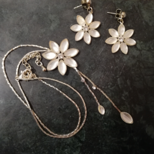 Matchande smyckes-set med halsband och örhängen. Silvrigt med vita blommor och strass. Frakt 9 kr.