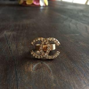 Chanel-ring fake i guld. Superfin och oanvänd. Går att ställa in storleksmässigt. Finns att hämta i Malmö, annars står köparen för frakt 💖