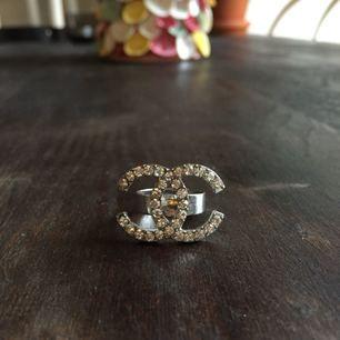 Chanel-ring fake i silver. Oanvänd. Går att ställa in storleksmässigt. Finns att hämta i Malmö, annars står köparen för frakt 💖
