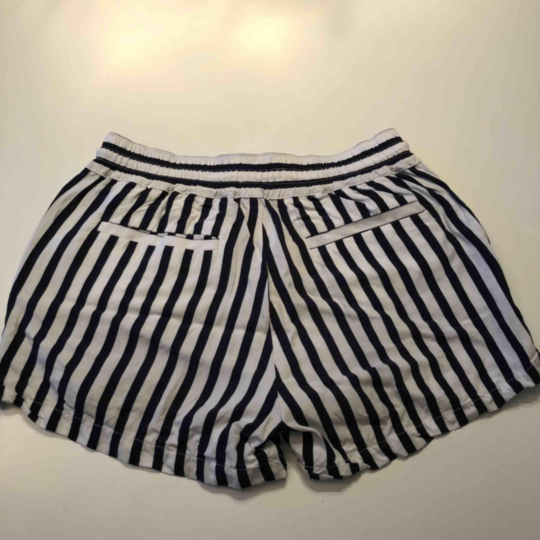Blå vita rangliga Tommy Hilfiger shorts! Shortsen är gjorda i tyg och är mycket luftiga på sommaren! Shortsen är också i ett mycket bra skick! . Shorts.