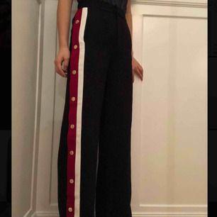 Snygga mörkblåa byxor med röda och vita revärer på sidorna och har även guld knappar på sidorna så man får bestämma hur mycket man vill öppna dem! Dem är även helt nya!