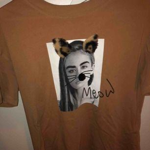 En brun T-shirt med tryck på tjej med lite utstickande material på framsidan! Köpt i grekland🙌🏻