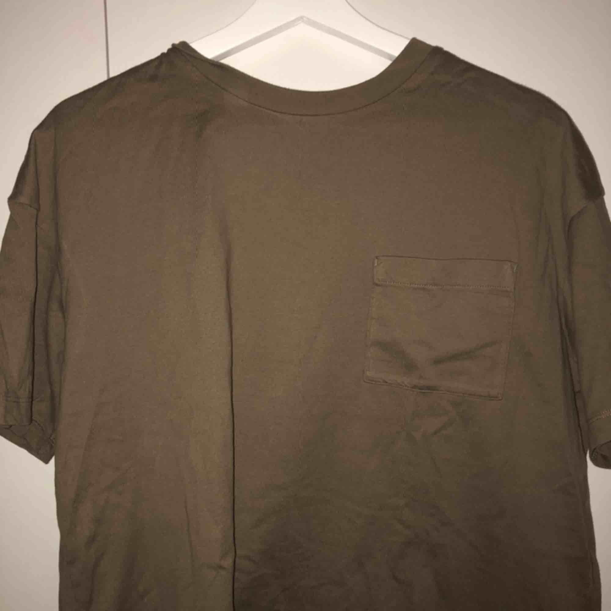 En brun/grön t-shirt. T-shirts.