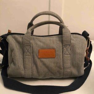 Klassisk randig blå vit randig väska med fejk skinn detaljer ifrån Zara. Har använt ett fåtal gånger. Bredd 24cm Höjd 19cm Bredd 12cm
