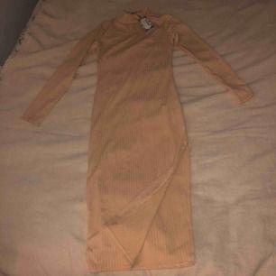 Aprikos färgad klänning med slits i sidan. Oanvänd med tags kvar.