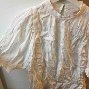 Asfin blus från H&M trend, i vitt lite shiny material (se bild 2). Jättefin modell med halvlånga ballongärmar och knappar längs båda sidorna. Helt oanvänd, lappen kvar! Ursprungspris 300kr.