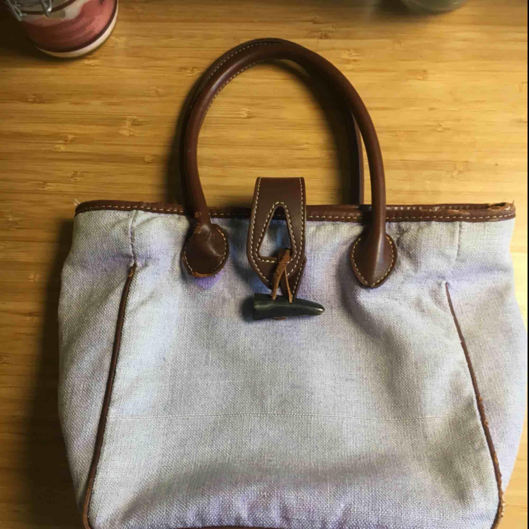 En väska som inte kommit till användning har hål kolla bild 1 och 3 . Väskor.