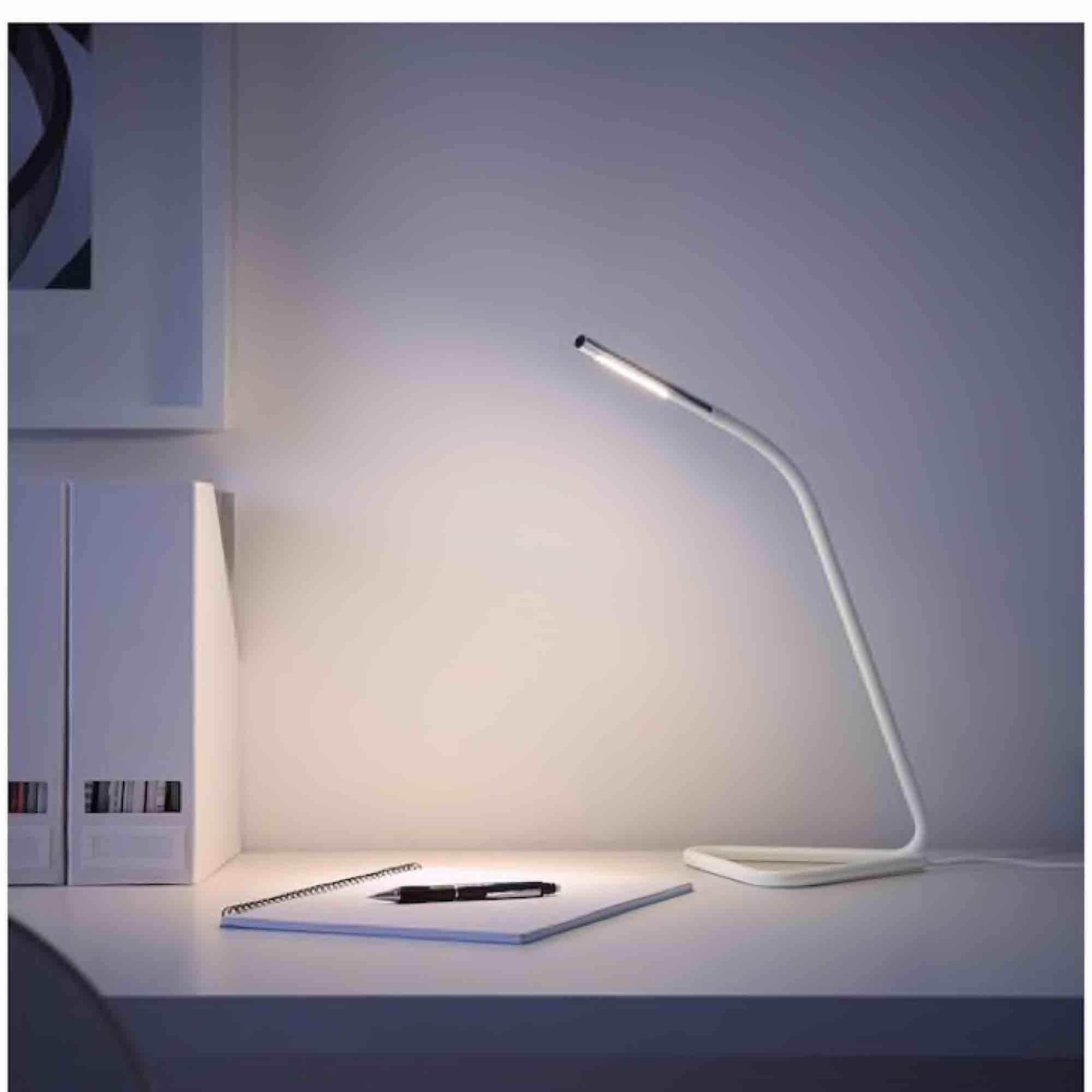 """Vit """"Hårte LED arbetslampa"""" från IKEA. Lampan kan ges ström via både ett vanligt vägguttag och USB-porten på dator. Lampans huvud är justerbart. Ljuset kan riktas både uppåt och nedåt.. Övrigt."""