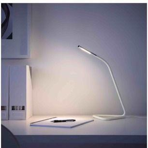 """Vit """"Hårte LED arbetslampa"""" från IKEA. Lampan kan ges ström via både ett vanligt vägguttag och USB-porten på dator. Lampans huvud är justerbart. Ljuset kan riktas både uppåt och nedåt."""