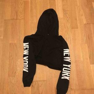 Normal svart hoodie, kort i midjan med luva. Står new york på ärmarna.