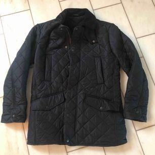 Oanvänd quiltad mörkblå Barbour jacka i storlek S. Innerfoder i fleece. Rak modell och därför stor i storleken, passar den som vanligtvis bär storlek M. Aldrig använd, perfekt skick