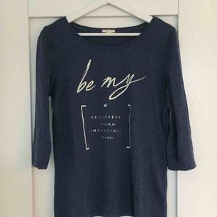 Marinblå 3/4 ärmad tröja från Esprit, med vitt tryck. Köparen står för frakten :)