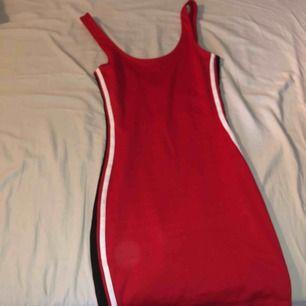 Supernsygg tajt röd klänning med 2 ränder längst med kroppen vid sidorna i svart och vit. Den följer ens kurvor perfekt! Använd 1 gång 🥰  Du står för frakten!