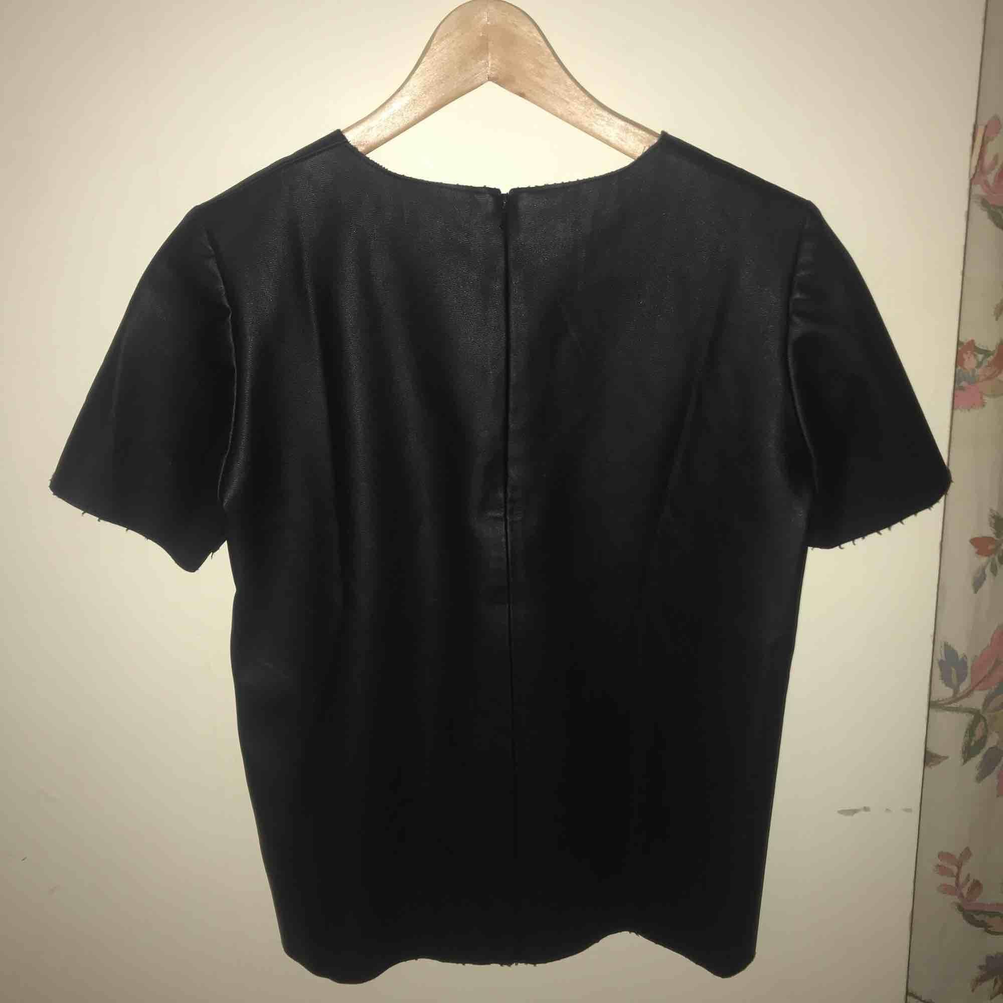 Skinnimiterad t-shirt topp i svart, använda ca 2 gånger. . Toppar.