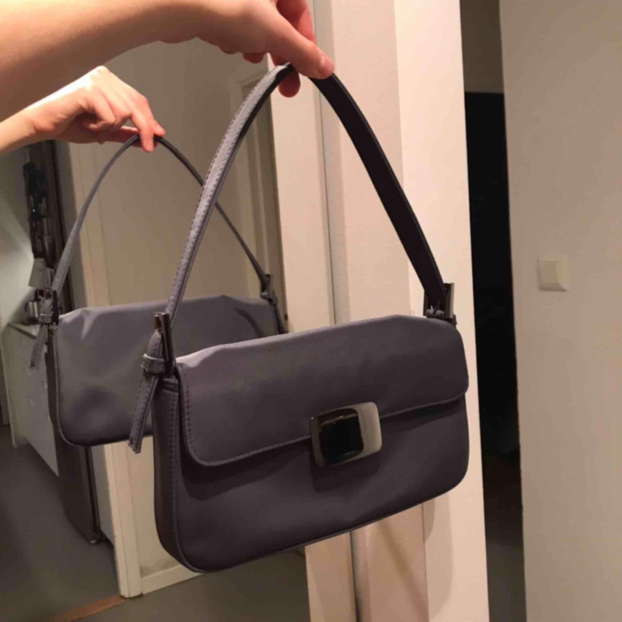 Asfin miniväska/shoulderbag i en gråblå färg, väskan är som ny! Lite repor på spännet men jag ser dem knappt🤪. Väskor.