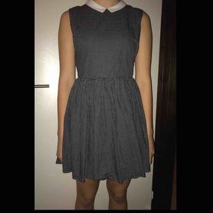 Svart vitprickig klänning med 50/60-tals stil. Min syster som bär den har storlek S/M och hon är 172 cm lång. Har används 2 gånger under skolans temadagar. Fraktavgift tillkommer och hör av dig om du vill ha detaljerade bilder eller har funderingar.