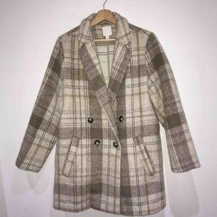 Snygg kappa från H&M som är i superbra skick, det står storlek 42 i jackan men skulle säga att den motsvarar en M ifall man vill att den ska sitta lite oversized.