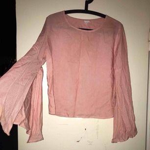 En tröja med utsvängda armar. Lite skrynklig eftersom den behöver strykas.