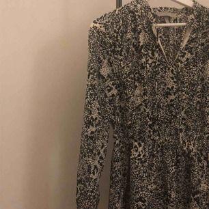 Långärmad klänning i trendigt snakeprint mönster. Går ner till slutet av låren ungefär. Väldigt skönt och luftigt material. Resårband i midjan, väldigt fin passform.